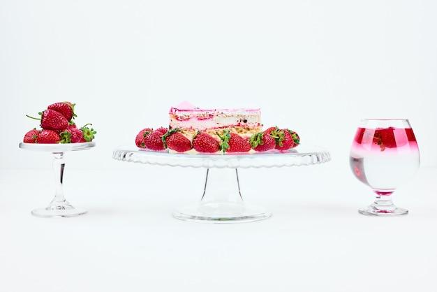 Una fetta di cheesecake alla fragola con frutta e un bicchiere di bevanda.