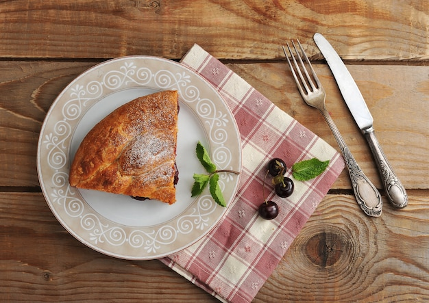 Slice of strudel with cherries on a plate