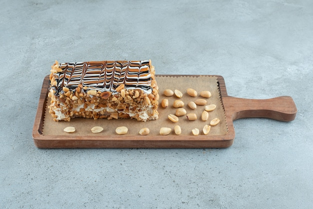 Slice of sweet cake on wooden board with peanuts. high quality photo