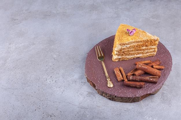 Fetta di torta dolce al miele con bastoncini di cannella su pietra.