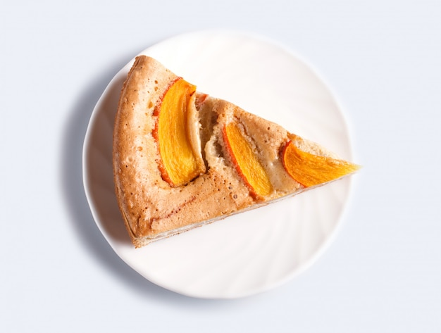A slice of  sweet persimmon pie isolated on white