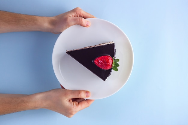 A slice of sweet strawberry cake with dripping chocolate glaze in a white plate in hands on blue