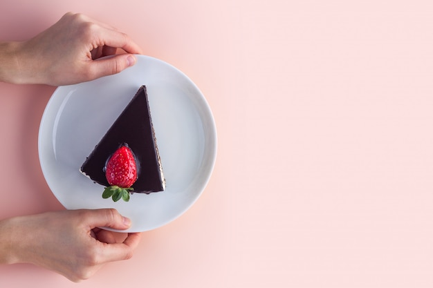 A slice of sweet strawberry cake with dripping chocolate glaze in a white plate in hands on pink