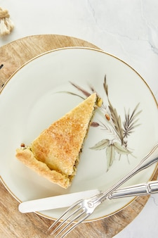 Slice of swiss pie with chard, rice, onions and pine nuts in plate on wooden stand on white marble. flat lay
