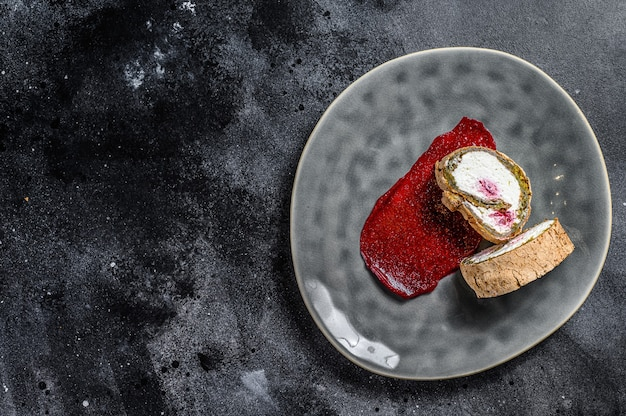 Slice of swiss roll with strawberry jam and cream. black background