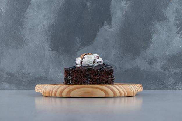 Fetta di gustoso brownie al cioccolato con crema su piatto di legno