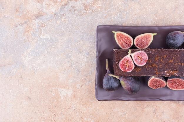 Una fetta di tiramisù con fichi viola sul piatto.