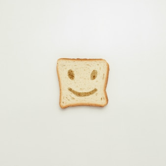 Slice of toast with cheerful smile on white