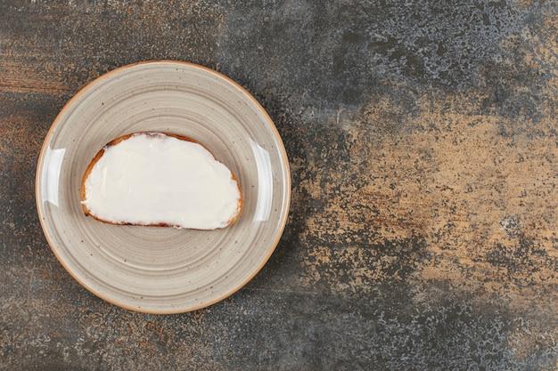 Fetta di pane tostato con panna acida sul piatto in ceramica.