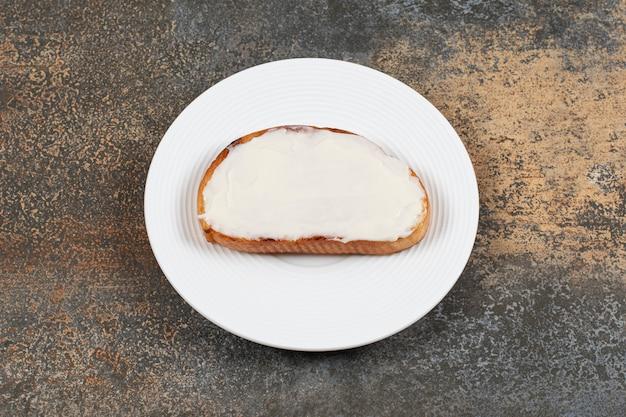 Fetta di pane tostato con panna acida sul piatto bianco.