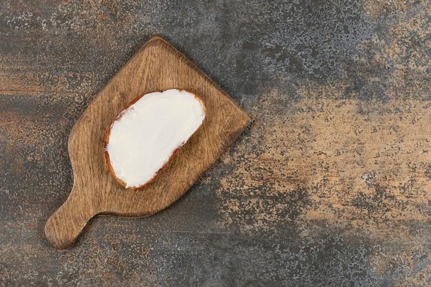 Fetta di pane tostato con panna acida su tavola di legno.