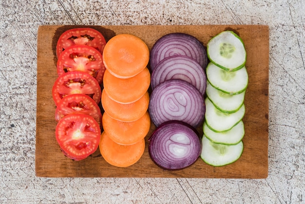Slice of tomatoes; carrots; onion and cucumber arranged on wooden board over the concrete backdrop