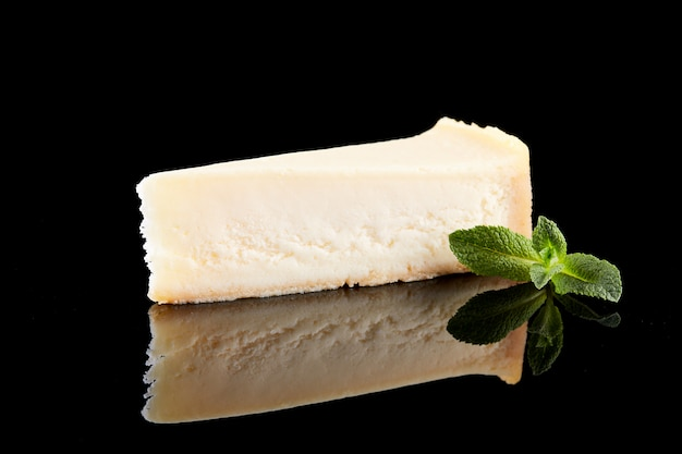 Slice vanilla cheesecake on black background.
