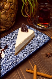 Slice of vanilla cheesecake on plate against a rustic brown wood table