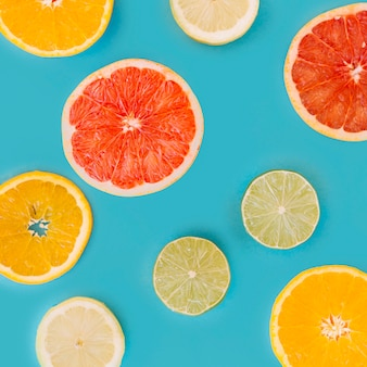 Slice of various citrus fruits on blue surface