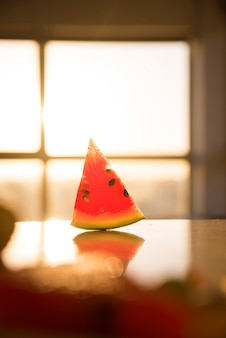 Slice of watermelon on the desk against the blur window