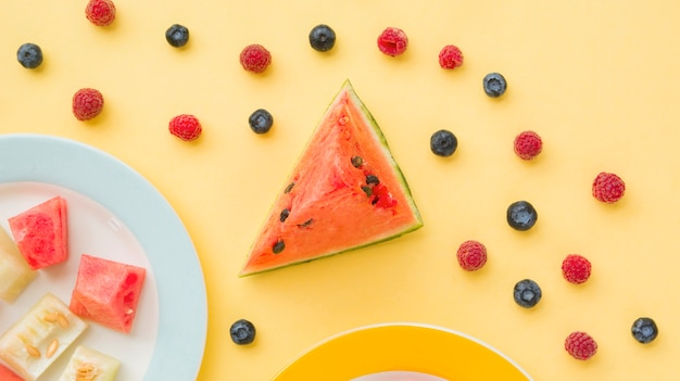 Slice of watermelon with blueberries and raspberries on yellow background