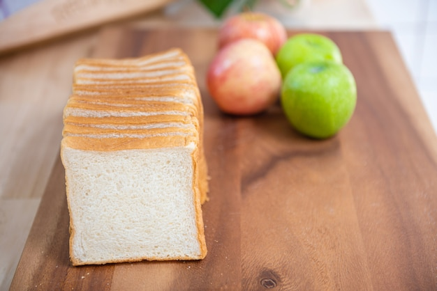 Slice white bread on cutting board with apples  and banana with bowl of fresh green salad in kitchen, healthy food concept.