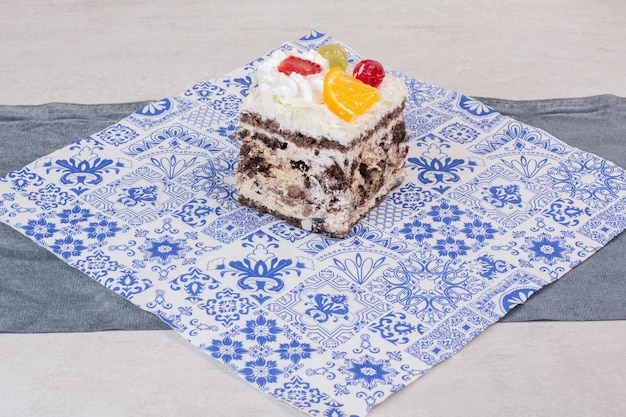 Slice of white cake with fruit slices on tablecloth.