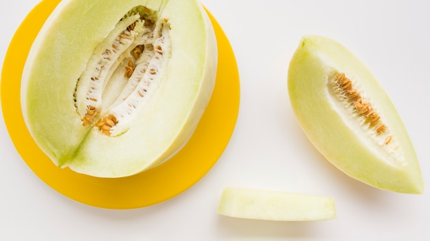 Slice and whole muskmelon on yellow plate over white backdrop