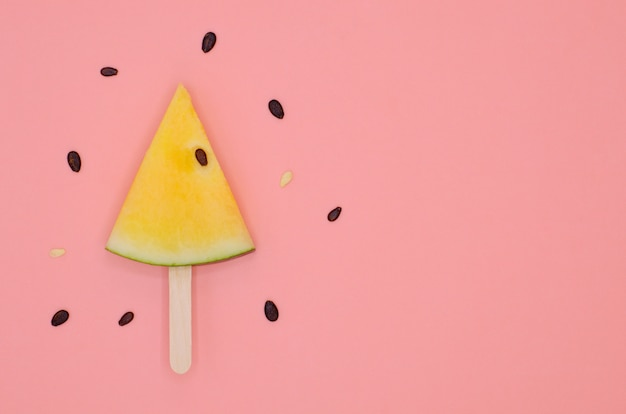 Slice of yellow watermelon on ice cream wooden stick with seeds for summer time.