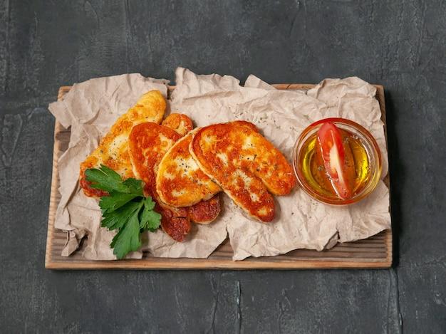 Нарезанный сыр халуми со специями. на деревянной доске. украшается специями и петрушкой. рядом с сыром стоит чашка с оливковым маслом. вид сверху. серый фон.