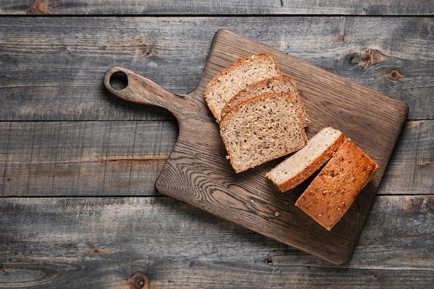 Нарезанный домашний цельнозерновой хлеб на деревянном столе. здоровая выпечка.