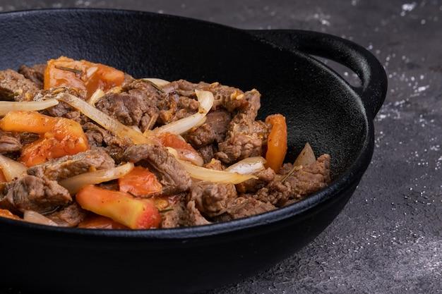 철 프라이팬에 얇게 썰어 튀긴 필레미뇽과 토마토, 양파.