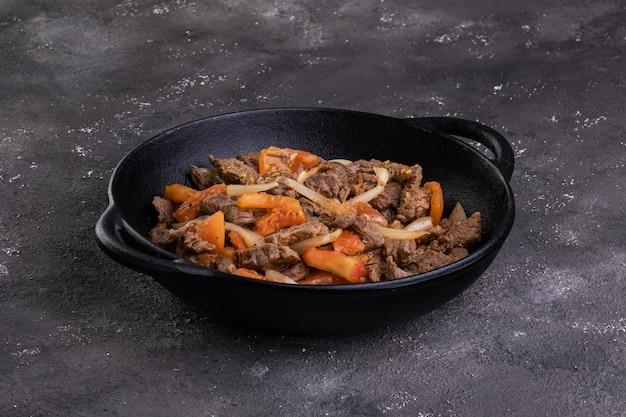철 프라이팬에 얇게 썰어 튀긴 필레미뇽과 토마토, 양파. 프리미엄 사진