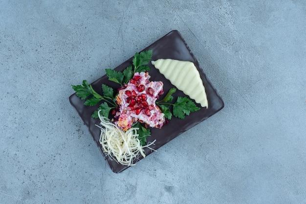 Нарезанный тертым сыр на черном блюде с небольшой порцией салата на мраморе.