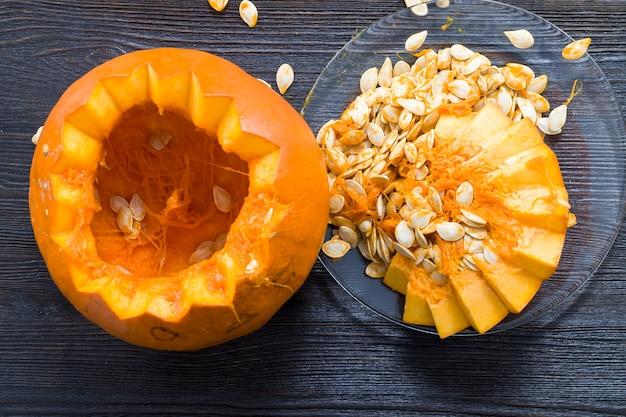 Нарезанная и потрошенная оранжевая тыква на кухонном столе, крупный план овощей, приготовленных для еды или сервировки