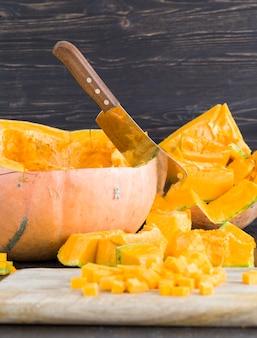 キッチンテーブルの上のスライスされた内臓のオレンジ色のカボチャ、食べ物や料理のために準備された野菜のクローズアップ