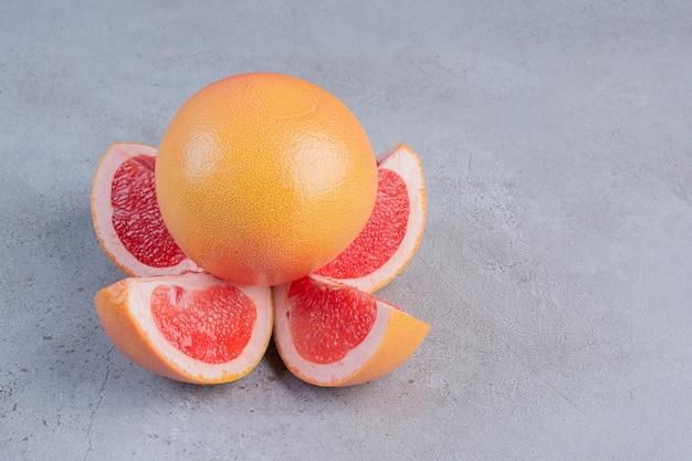 大理石の背景に表示されるスライスされた全体のグレープフルーツ。