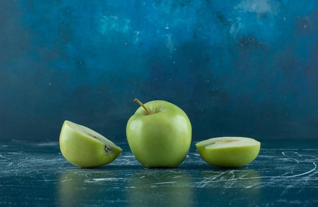 Нарезанные и целые зеленые яблоки на мраморном столе.