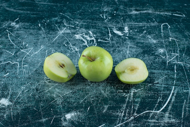 대리석 테이블에 슬라이스 및 전체 녹색 사과.