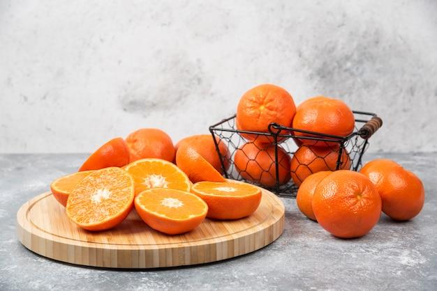 Нарезанные и целые сочные свежие плоды апельсина на каменном столе.