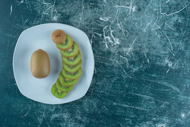 Нарезанные и целые киви на тарелке, на мраморном столе.