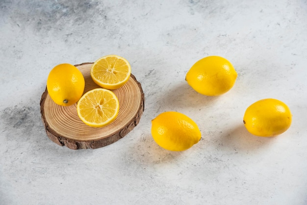 Нарезанный и весь лимон на мраморном фоне.