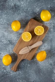スライスしたレモン全体と木製のジューサー。