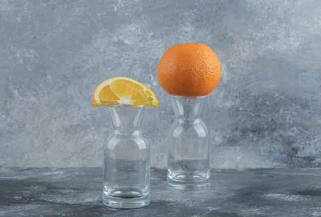 Нарезанный и целый апельсин поверх пустого стакана.
