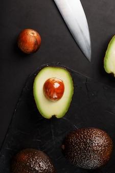 검은 표면에 칼로 슬라이스 및 전체 유기농 아보카도 hass. 필수 지방, 비타민, 미량 원소, 베타 카로틴 및 오메가 -3 지방산의 공급원입니다.
