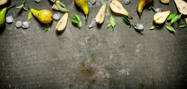 Нарезанные и целые груши со льдом и листьями. на каменном столе. свободное место для текста. вид сверху