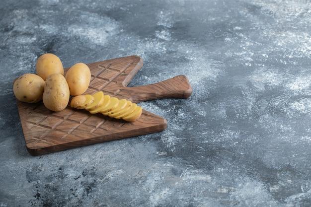 木製のまな板にスライスしたジャガイモ全体。高品質の写真