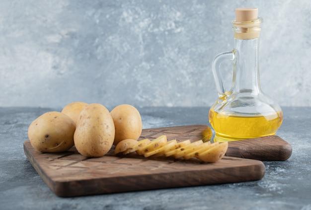 나무 커팅 보드에 슬라이스 및 전체 감자. 고품질 사진
