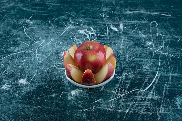흰색 그릇에 슬라이스 및 전체 빨간 사과입니다.