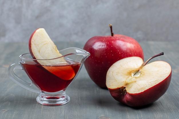 주스와 함께 슬라이스 및 전체 빨간 사과