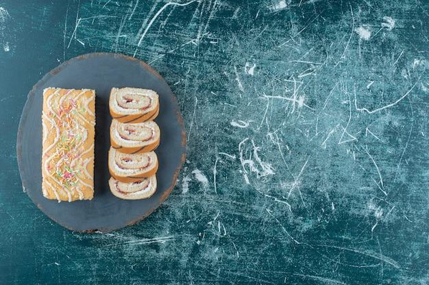 파란색 배경에 보드에 얇게 썬 전체 롤 케이크. 고품질 사진