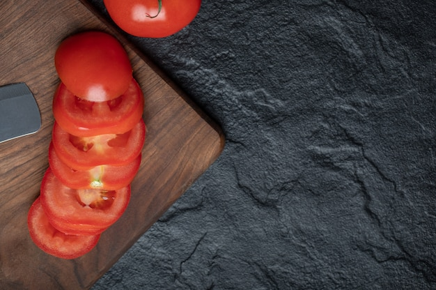 Sliced appetizing tomato on cutting wood. high quality photo