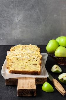 暗い背景の木製まな板にスライスしたリンゴとココナッツオークケーキ。コピースペース