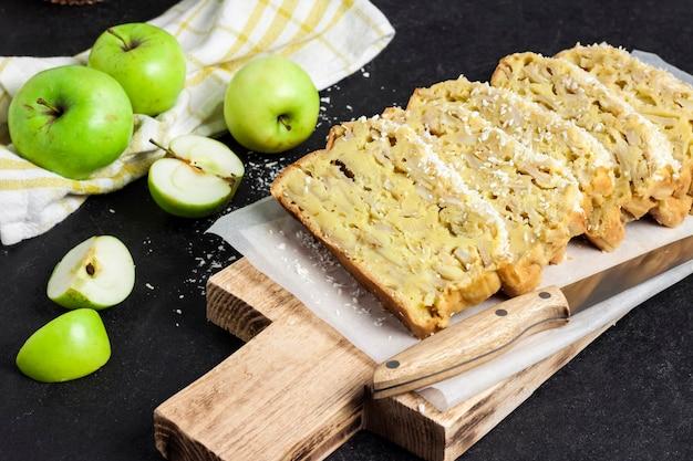 暗い背景の木製まな板にスライスしたリンゴとココナッツオークケーキ
